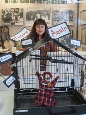 Lillian Halden, an eighth-grade language-arts teacher at Rosa International Middle School in Cherry Hill, stands by project made by student Matthew Merovitz that is displayed in the Goodwin Holocaust Museum and Education Center in the Katz Jewish Community Center in Cherry Hill.  Halden will be one of 500 community members taking part in the 3rd Annual March of Remembrance Walk.