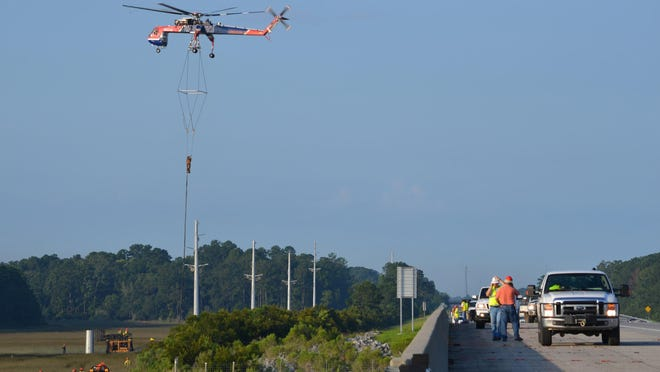 Hovering above the coastal salt marsh alongside Interstate 95 between Bryan and Liberty counties, an air-crane helicopter works to position 80- to 100-foot steel poles into the ground for Coastal Electric Cooperative. The poles not only bring electricity to homes and businesses, but a 96 strand fiber optic cable encased within the 115,000-volt line will become the backbone that will deliver access to broadband internet.