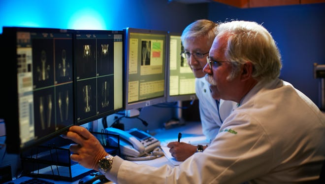 Tim Manzone, M.D., J.D., section chief of Nuclear Medicine at Christiana Care, reviews images of bones with fellow nuclear medicine specialist Hung Dam, M.D.
