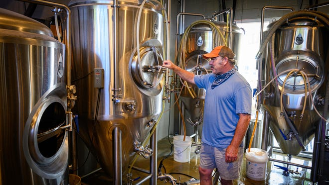 Matt Hooker, co-owner of Old Coast Ales, checks on a fermentation tank in his brewery on Anastasia Boulevard in St. Augustine on Friday.