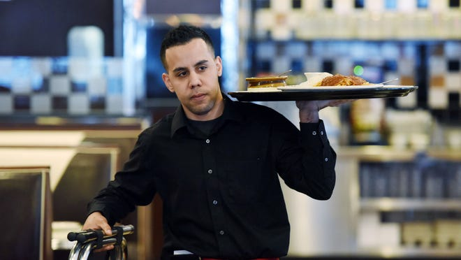 Table Talk Diner server Jose Fenandez of Fishkill carries meals to customers on Monday at the restaurant in the Town of Poughkeepsie.