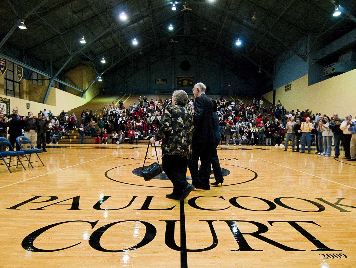 "Former Lansing Eastern Head Basketball Coach Paul Cook (right) and his wife Mary Ellen walk onto the court at Don Johnson Field House during the ceremony naming the court there the ""Paul Cook Court"" on February 27, 2009 at Eastern High in Lansing."