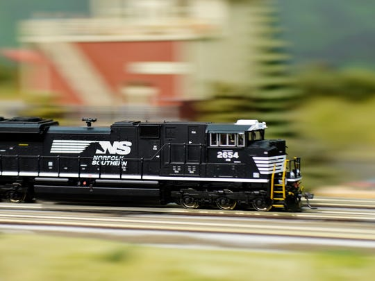A model train rushes past a mountain landscape during