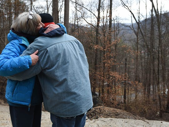 Sue Thompson hugs her son Ben Thompson as they revisit their home Friday, Dec. 9, 2016, in Gatlinburg, Tenn. Volunteers with All Hands and Reach Out Worldwide were helping to clear trees and will sift through the remains of the family home.