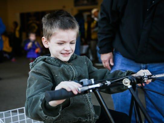 Elijah Nobles, 7, rides his new tricycle Saturday,