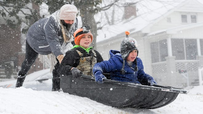 Amanda Buckler, left, helps push Kyler Latham, center, and Wyatt Fetscher, right, down Reitz Hill while sledding on Friday.