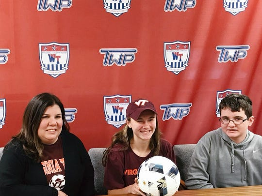 Emily Gray poses with her mother, Laurie (left), and brother, Carson, when she signed her letter of intent to Virginia Tech.