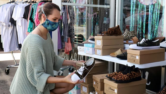 Katelynn Lindley sets up a sales rack, Saturday, August 1, 2020, at Van Buren's La Boutique, for the Arkansas' Tax-Free Weekend through Sunday, August 2, 2020. Currently, Arkansas statewide tax is 6.5%, while the average local sales tax is 2.1%. Shoppers will save an average of around 9% on qualifying purchases over the weekend. Qualifying online purchases will also be tax-free if the order is delivered to an Arkansas address. Tax-free items include, clothing, clothing accessories or equipment, school instructional materials, art supplies and common school supplies.