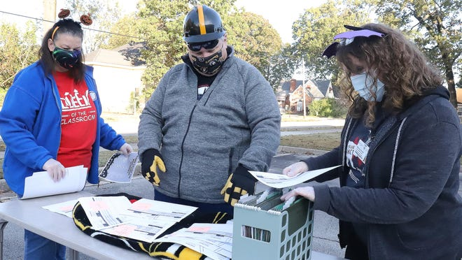 Dressed in Halloween costumes, Fort Smith Public School teachers Melissa Knight, from left, Jonathan Mathis and Donna Smith set up outside of the Rogers Center, Friday, Oct. 30, handing out report cards during the virtual student report card drive-thru.