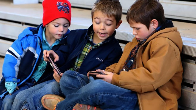 Anthoney Jobe, from left, Matthew Pecora and Blane Blackstock play video games, Saturday, Oct. 31, as their families ride in the U.S. Mounted Shooting event at Kay Rodgers Park. Anthoney is the 5-year-old son of Angela and Matthew Jobe of Windsor, MO, Matthew is the 7-year-old son of Angie and Kenny Pecora of Caboul, MO and Blane is the 7-year-old son of Randi and Billy Wayne Blackstock of Wheeler, Texas.