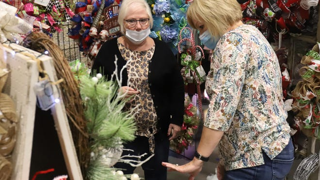 Wanda Gilstrap, left, and Sherri Prentice set out holiday wreaths for sale at  Wanda's Wandering Threads & More vendor booth, Saturday, Nov. 14, during the Poteau Holiday Market 2020 at the Poteau Reynolds Center.