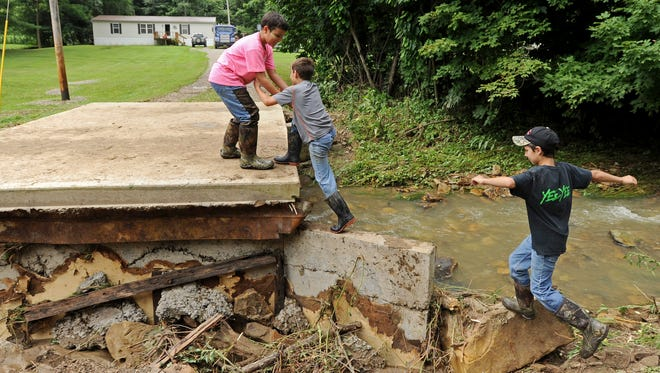 Climbing up what remains of Jason McCorkle's driveway made of concrete and large stones on Bishop Hill Road are, from left, Collin Jones, 10, Dalton McCorkle, 9, and Trevor McCorkle, 10. McCorkle's driveway, which forms a bridge over a creek, was washed away Sunday night during the rainstorm that hit the area. In addition to flooding the neighborhood has had to deal with fallen trees, branches and other debris.