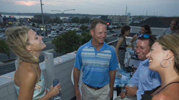Two Seas patrons  enjoy cocktails and conversation during a private party on the deck in Dewey Beach.