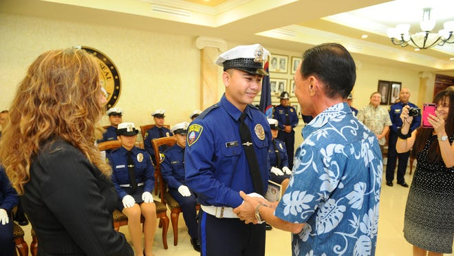 Guam Police officer trainee Joshua Togawa gets a congratulatory handshake from his father, retired Guam Police Department Maj. Jesus Togawa, during the 6th Police Officer Trainee Cycle graduation ceremony at the Government House in Agana Heights on Friday, Sept. 25.