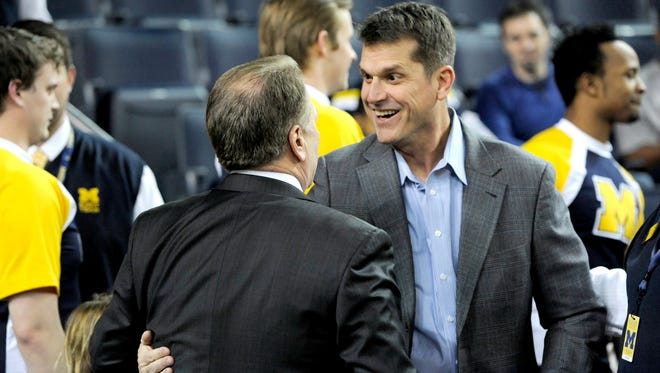 MSU head coach Tom Izzo greets new  Michigan football head coach Jim Harbaugh at Crisler Arena before the MSU/Michigan basketball game  Tuesday   2/16/2015.  (Rod Sanford/Lansing State Journal)