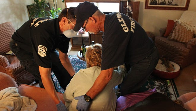 Glendale firefighters Roman Barriga and Roger Thompson help an elderly woman stand before taking her to an ambulance in Glendale, Arizona on October 21, 2015.