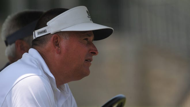 Skip Runnels watches as Derek Moore tees off during the Wayne County amateur golf tournament at Forest Hills Country Club.