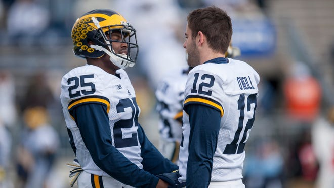 Michigan safety Dymonte Thomas warms his hands in the pouch of Michigan punter Blake O'Neill during pregame warm-ups Saturday.