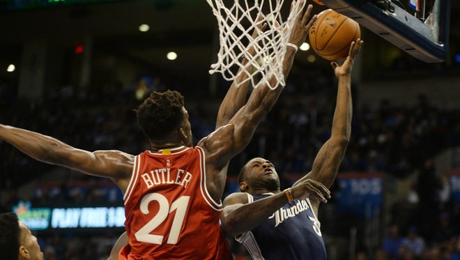 Chicago Bulls guard Jimmy Butler (21) contests a shot attempt by Oklahoma City Thunder guard Dion Waiters (3) during the first half of a NBA basketball game on Christmas at Chesapeake Energy Arena.