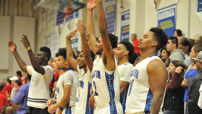 Members of the Stephen Decatur boys basketball team celebrate during their win against Centennial in the 3A East Region final on Saturday in Berlin.