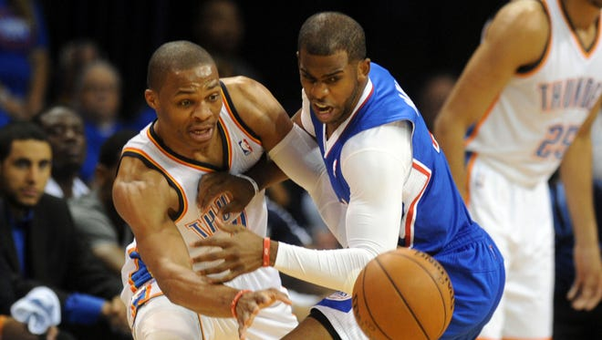 May 5, 2014; Oklahoma City, OK, USA; Oklahoma City Thunder guard Russell Westbrook (0) loses the ball while being guarded by Los Angeles Clippers guard Chris Paul (3) during the first quarter in game one of the second round of the 2014 NBA Playoffs at Chesapeake Energy Arena. Mandatory Credit: Mark D. Smith-USA TODAY Sports