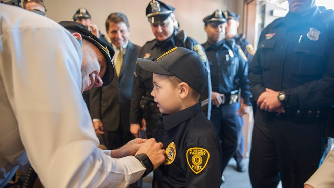 Lt. Brendan Barton helps 7-year-old honorary police officer Liam Lindsey of Gloucester Twp. with his uniform as Lindsey is sworn in by Gloucester Township Mayor David Mayer and Chief Harry Earle at the Gloucester Township Police Department. Monday, March 21, 2016.