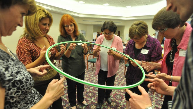 Participants in the Institute for Creative Leadership use a hula hoop during an exercise.