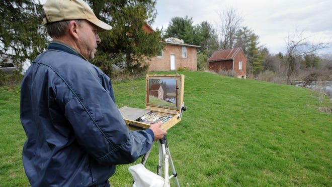 Patrick Sims sets up to continue work on a painting Thursday at a farmhouse on Anderson Station Road. Sims specializes in outdoor painting.