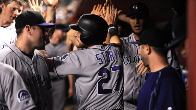 Apr 30, 2016: Colorado Rockies shortstop Trevor Story (27) slaps hands with teammates after scoring a run in the ninth inning against the Arizona Diamondbacks at Chase Field.
