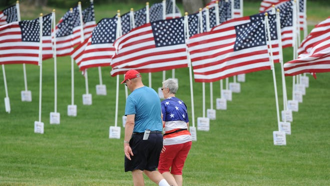 "Spectators walk past ""The Field of Flags"" created by The Twin City Exchange Club and Lest We Forget, as a tribute for Memorial Day, near the eighth hole during the third round of the Senior PGA Championship, May 28, 2016, at The Golf Club at Harbor Shores, in Benton Harbor, Mich."