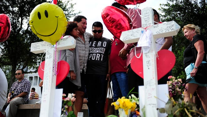 Mourners support each other at the cross of Joel Rayon Paniagua at a memorial Sunday, at Orlando Regional Medical Center in Orlando, Fla. Paniagua was one of 49 killed by shooter Omar Mateen at Pulse nightclub –on June 12.
