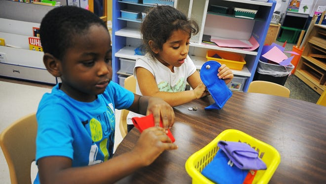 Irshad Kalombo, 4, left, and Alyvia Weyh, 5,  work with tag bags to learn about numbers during the work group portion of Jessica Ballard's early childhood class for kids age three to five Monday, Feb. 1, 2016, at Harvey Dunn Elementary School in Sioux Falls.