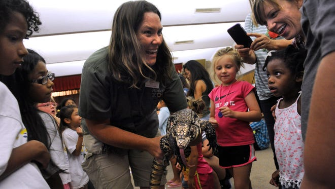 Joy Harsh, education curator for the Abilene Zoo, shows a black and white tegu to children during a presentation Tuesday July 18, 2017 at the Abilene Public Library's Main Branch. Harsh also brought a California kingsnake, a Columbian Wyandotte chicken, and a pair of Norwegian rats. Harsh will be bringing animals to the South Branch Library at the Mall of Abilene at 4 p.m. July 26.