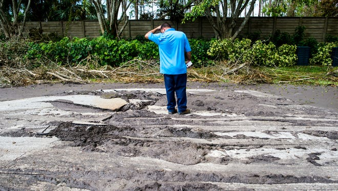 A Collier County worker observes where sewage broke through Mahogany Bend Drive in Naples on Thursday, Sept. 14, 2017.