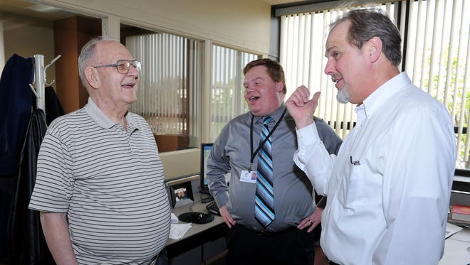 Jim Hough, left, and Mark Mayes, center, laugh at a story John Schneider is telling on John's last day at the Lansing State Journal, April 13, 2012.