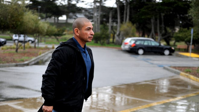 Johnny Placencia walks through the rain into the Marina Public Library.