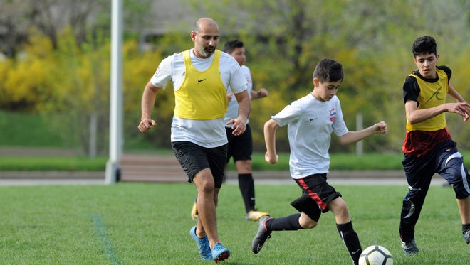 Michigan Futball Club, founder Abbas Al-Wishah, left, plays in a soccer scrimmage with a group of kids that he coaches. According to Al-Wishah, refugee kids of various ages in his league are from more than a dozen countries.