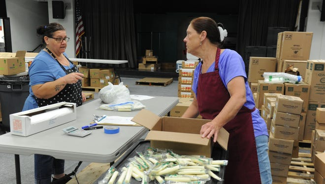 From left, child nutritional workers Susie Contreras and Ann Martinez prepare string cheese for the summer meals program in the Ventura Unified School District.