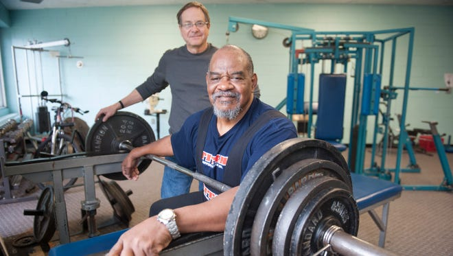 Powerlifter Charles King, a blind and formerly homeless veteran, works out at the Carousel House in Philadelphia as GW Stilwell, a Logan Township man and VA Hospital employee who helped King get back on his feet, looks on. King is trying to fundraise his way to the International Blind Sports Association's World Games in South Korea in May.