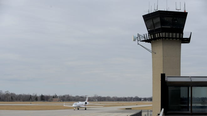 A plane taxis past the tower at Detroit City Airport.