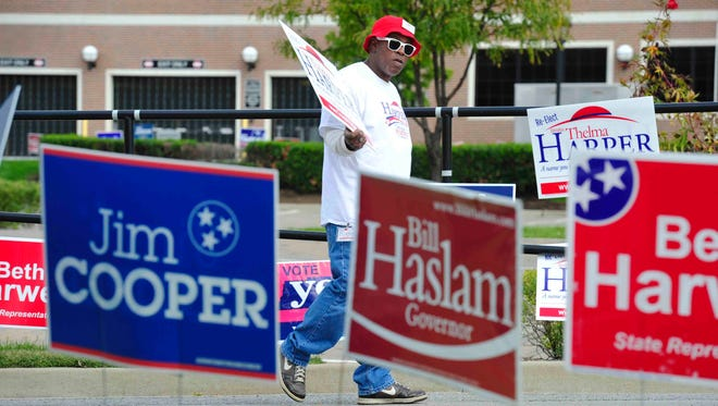 George Washington holds a Thelma Harper sign in the parking lot during early voting Oct. 17 at the Howard Office Building.