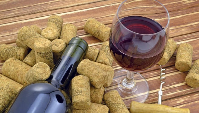 Glass of wine on background of bottle and corks