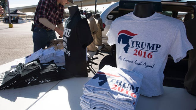 Vendor Jonathan Maney, of Fort Walton, sets-up to sell a variety of Trump memorabilia outside the Pensacola Bay Center Wednesday morning.