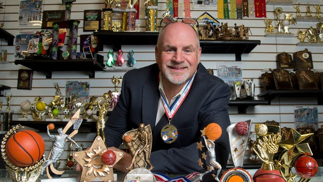 Keith Baldwin, 58, chief relationship officer for Spike's Trophies, poses for a portrait surrounded by participation trophies on the counter. Baldwin participated in a triathlon recently and made a participation medal (like the one hanging around his neck) for himself.