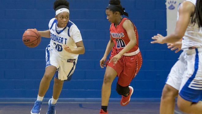 Janelle Jones (10) dribbles past Lisa Merriel (00) during the Region 1-7A quarterfinal girls basketball game between Washington and  Fort Walton Beach at Booker T. Washington High School in Pensacola on Thursday, February 15, 2018.