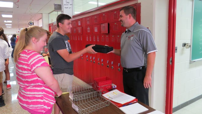 Jack Depner, Port Clinton High School freshman, receives his Chromebook laptop computer from Todd Buck, assistant principal.  At left is Sheridan York, next to receive her Chromebook.