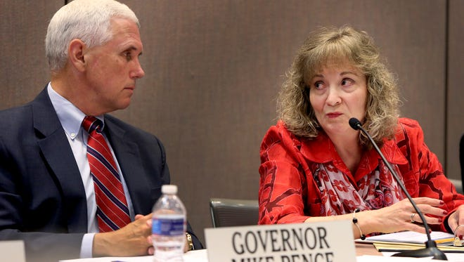Republican Gov. Mike Pence and Superintendent of Public Instruction Glenda Ritz are shown at the Indiana Education Roundtable meeting at the Indiana Government Center in Indianapolis on June 23, 2014. Pence on Thursday signed a bill into law that will strip much of the control of education policy away from Ritz, a Democrat, and also change the makeup of the State Board of Education.