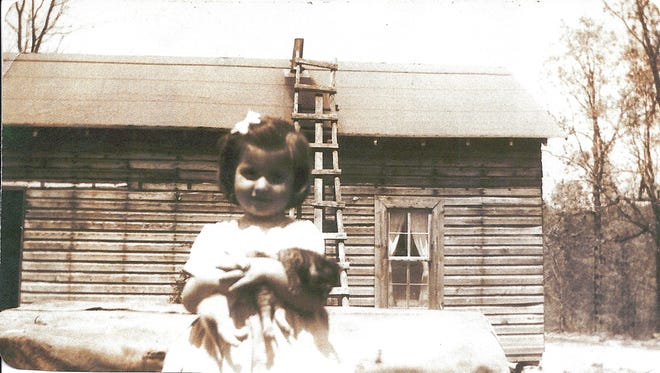 Linda Bradbury, about 3 years old, at the little house on the hill.