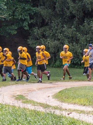 Battle Creek Central football players run to the practice field during their 3 day football camp at Clear Lake Camp.