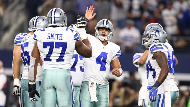 Dallas Cowboys quarterback Dak Prescott (4) high fives tackle Tyron Smith (77) in the huddle against the Tampa Bay Buccaneers at AT&T Stadium. Mandatory Credit: Matthew Emmons-USA TODAY Sports